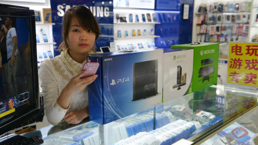 A vendor sells game consoles including Xbox One and Sony's PS4 which they say enter China through unofficial channels in Shanghai on January 8, 2014.