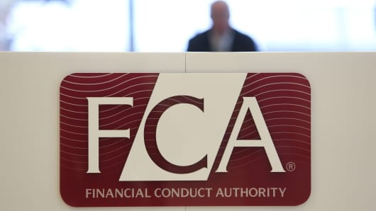 A logo sits on a sign in the reception area of the headquarters of the Financial Conduct Authority (FCA) in the Canary Wharf business district in London, U.K.