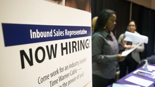 A 'Now Hiring' sign stands at one of the exhibitors tables at the Columbus Career Fair in Columbus, Ohio.