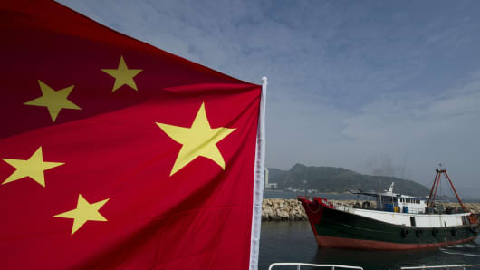 A fishing boat (R) sails past another boat flying a Chinese flag in the East China Sea
