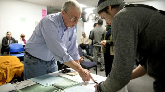Volunteer Tony Hausner, left, assists an enrollee at a health insurance event in Silver Spring, Md.