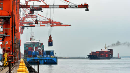 Shipping containers are unloaded from an international freighter while another cargo ship (R) arrives at the international cargo terminal in Tokyo on October 21, 2013.