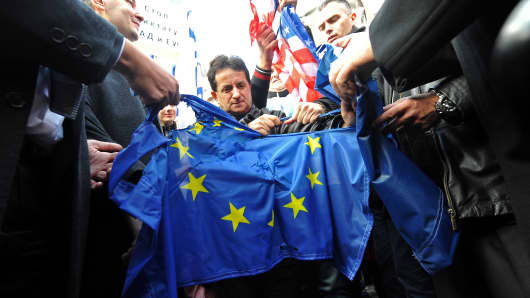 Supporters of the nationalist Serbian Radical Party (SRS) rip apart the EU flag.