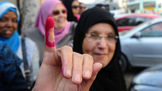 A woman outside a Cairo polling station shows her ink-stained finger after voting on a new constitution on Jan. 14, 2014.