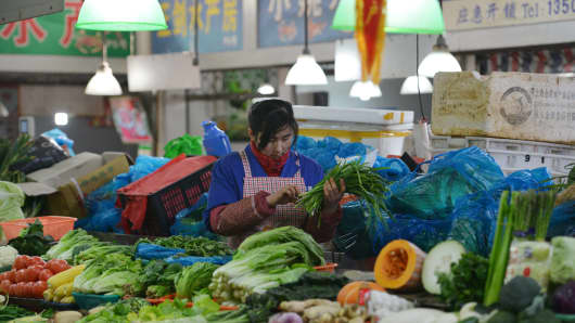 A vendor sells vegetables in a market in Shanghai on January 9, 2014.