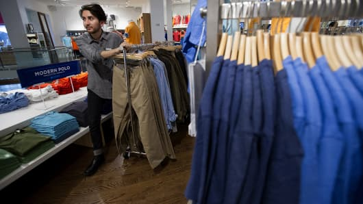 An employee pushes a rack of clothes inside a Gap Inc. store in San Francisco.