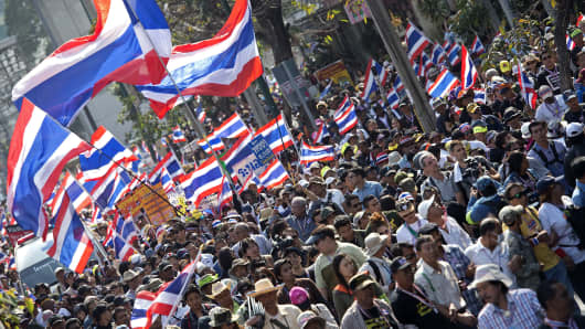 Thai anti-government protesters wave national flags as they parade during a rally in Bangkok on Saturday.