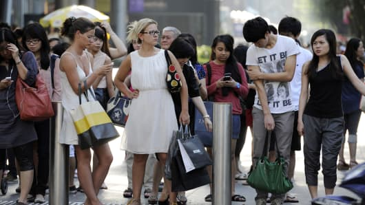 Shoppers and pedestrians wait to cross a road on Orchard Road in Singapore.