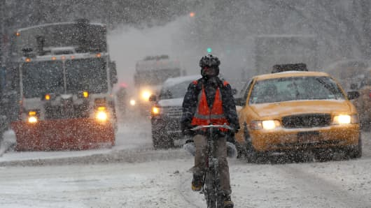 A man rides a bicycle in Manhattan during a snowstorm that is moving through the Northeast on January 21, 2014 in New York City.