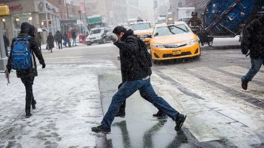 Two people jump over a puddle during a snowstorm that is moving through the Northeast on January 21, 2014 in New York City.