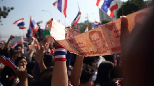 A strip of Thai bank notes are passed from supporters as a donation to anti-government leader Suthep Thaugsuban during a march in downtown Bangkok on January 22, 2014, as part of ongoing rallies.