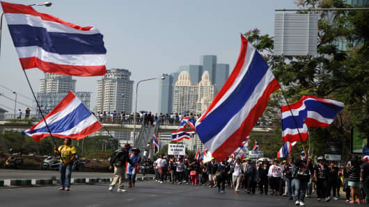 Anti-goverment protesters wave Thai national flags during a march in downtown Bangkok as part of their ongoing rallies.