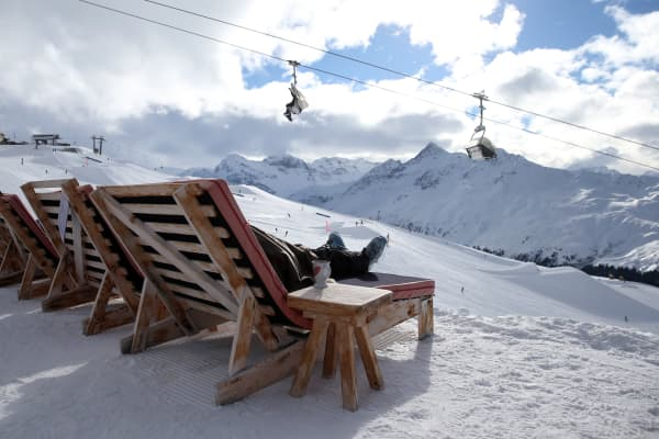 A woman rests on a sun chair at the top of the Jakobshorn mountain in Davos, Switzerland.