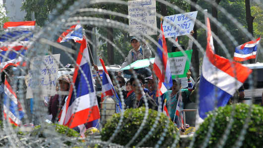 Anti-government protesters wave national flags as they block the street in front of the Office of the Defence Permanent Secretary during a rally in Bangkok on January 22, 2014.