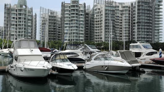 Yachts at ONE°15 Marina Club at Sentosa Cove during the Singapore Yacht Show 2011 are anchored against the backdrop of luxury condominiums, in Singapore, on Sunday, April 10, 2011.