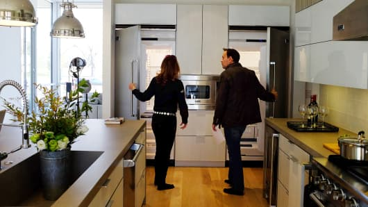 Prospective home buyer, left, looks at the refrigerators of a new home for sale while speaking with a realtor in Denver, Colorado.
