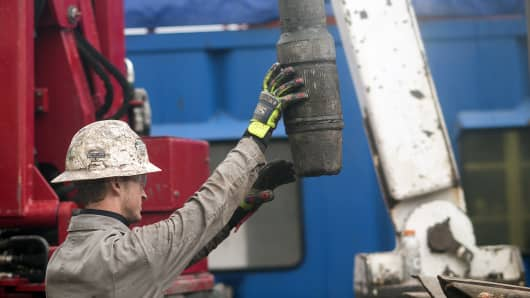 A rig hand removes drill pipe from a natural gas well at a hydraulic fracturing site in Washington Township, Pennsylvania.