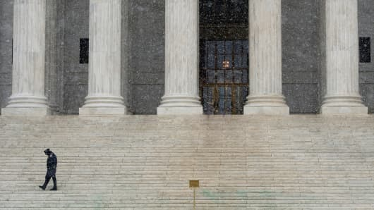 A U.S. Supreme Court police officer paces along the steps to the court as snow falls on Tuesday, Jan. 21, 2014.