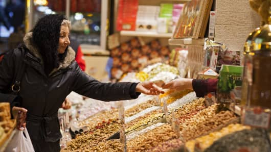 A customer receives her change in Turkish lira after purchasing goods in a spice market in Istanbul, Turkey.