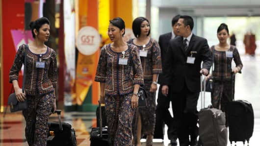 Singapore Airlines Ltd. flight staff walk through Changi Airport in Singapore, on Wednesday, July 27, 2011.