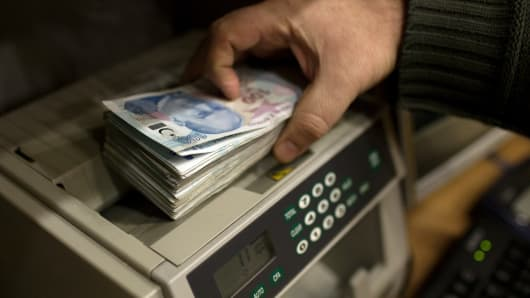 An employee uses a machine to count a bundle of 100 Turkish lira banknotes inside a currency exchange office in Istanbul, Turkey.