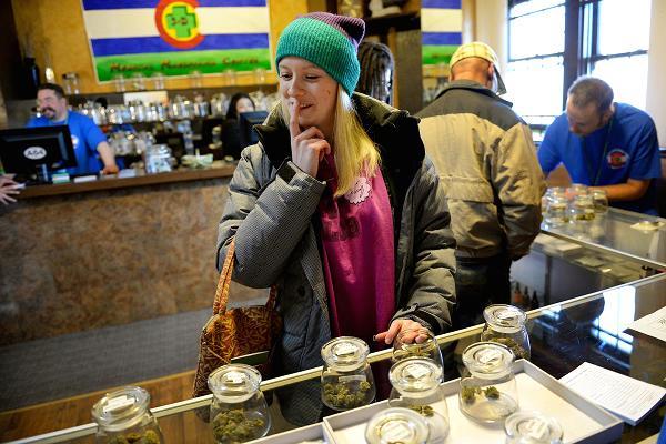 Kristin Brinckerhoff ponders the selection of marijuana at 3D Cannabis Center in Denver, Jan. 2, 2014.
