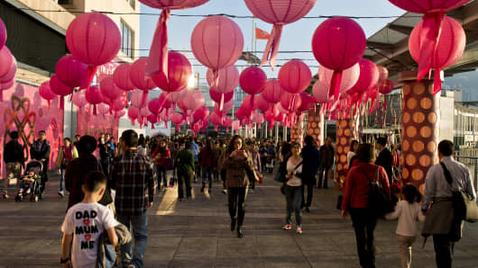 This photo taken on January 31, 2014 shows people walking under lanterns and decorations set up to celebrate the Lunar New Year in Hong Kong. Chinese communities across Asia came together to usher in the Year of the Horse, with millions across China returning home to mark the holiday with their families.