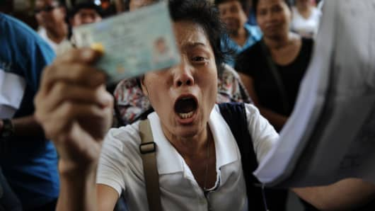 A frustrated Thai voter holds her national identification card and shouts at police blocking the entrance to a polling station as voting was cancelled after anti-government protesters prevented the delivery of election material in downtown Bangkok on February 2, 2014.