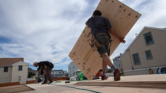 A construction worker carries a sheet of plywood as he and co-workers install the sub-floor of a home onto pilings.