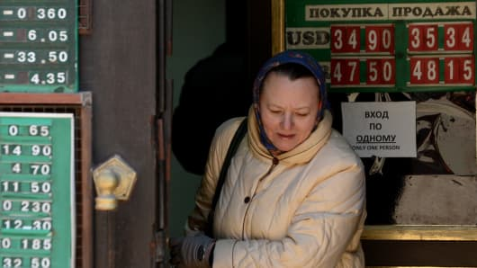 A woman walks past the boards listing foreign currency rates against the Russian ruble as she leaves an exchange office in central Moscow, on January 31, 2014.