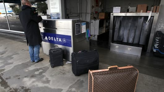 A Delta Airlines customer checks his baggage before a flight at San Francisco International Airport (SFO).