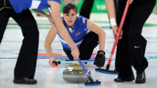 Allison Pottinger releases the stone as Nicole Joraanstad (L) and Natalie Nicholson brush the ice during a Women's Curling match between Germany and the U.S. during the 2010 Winter Olympics.