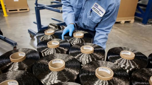 An employee prepares spools of carbon fiber for shipment at the SGL Automotive Carbon Fibers manufacturing plant in Moses Lake, Washington.