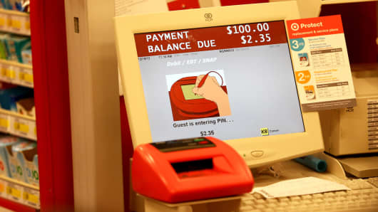 A cash register screen indicates a customer is entering their PIN number at a Target store in Miami.