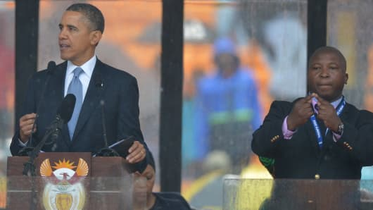 President Barack Obama speaks, with purported sign language interpreter Thamsanqa Jantjie standing behind at the memorial service for late South African President Nelson Mandela