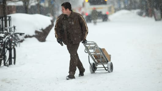A UPS worker makes deliveries Wednesday in Burlington, Vt.