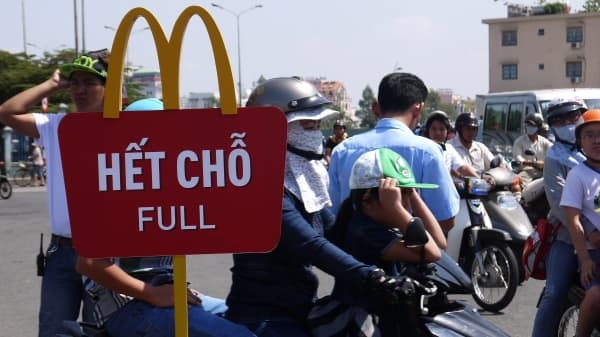 People arrive on motorbikes at the first McDonald's restaurant opening in Ho Chi Minh city on February 8, 2014.