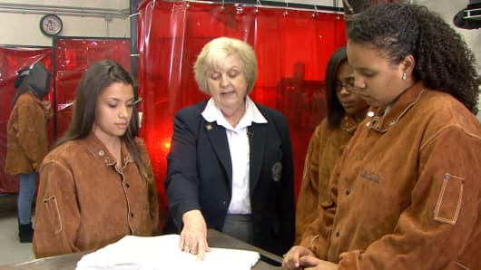 Recent American Welding Society President Nancy Cole works with high school students inside a Miami welding shop.