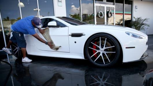 Rubin Viart washes an Aston Martin vehicle on the sales lot of Brickell Luxury Motors on Jan. 2, 2014, in Miami.