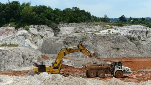 An excavator loads stripped overburden onto a dump truck in the mine pit at the PT Timah operations in Sungai Liat, Bangka Island, Indonesia.