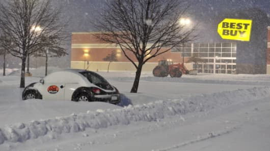 A worker plows snow from a parking lot during a major snowstorm on Thursday in Manassas, Va.