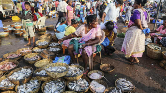 A vendor sits waiting for customers at the wholesale fish market in Margoa, Goa, India.