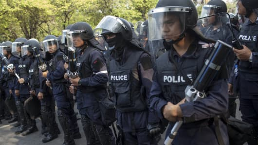 Police move in formation as they shut down and break apart an anti-government protest site near Government House in Bangkok on February 14, 2014.