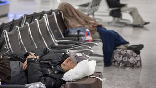 Storm-weary travelers sleep in the baggage claim area at Dulles International, Feb. 13, 2014.