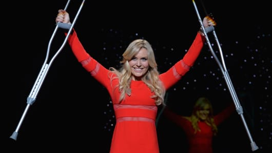 Skier Lindsey Vonn raises her crutches as she presents a dress by Cynthia Rowley during The Heart Truth Red Dress Collection show sponsored by the American Heart Association Go Red For Women campaign February 6, 2014 in New York.