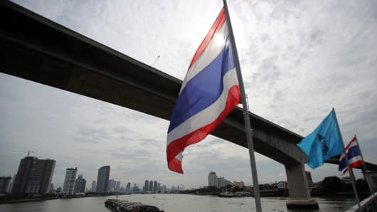 The Thai national flag flies on the Krungthep Bridge as a barge is pulled under the Rama III Bridge on the Chao Praya river in Bangkok, Thailand.