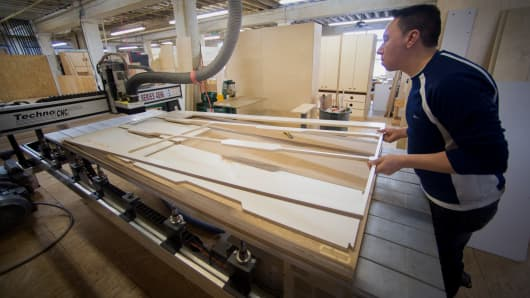 A worker handles a CNC router, a computer controlled cutting machine, to build a piece of furniture at Casa Kids' Red Hook facility in the Brooklyn borough of New York.