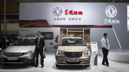 Employees stand at the Dongfeng Motor Corp. booth at the 11th China (Guangzhou) International Automobile Exhibition in Guangzhou, China.