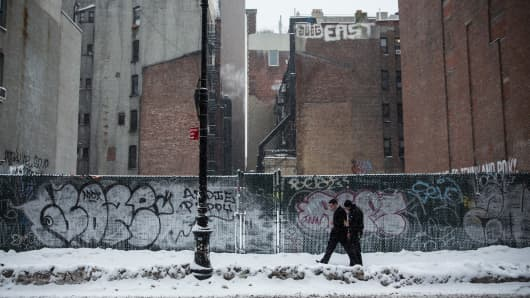 People walk through snowfall in New York City.
