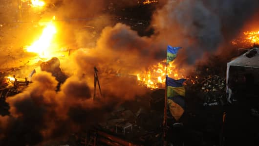 A Ukrainian flag stands as anti-government protesters clash with police in the early morning hours of February 19, 2014 in Kiev, Ukraine.